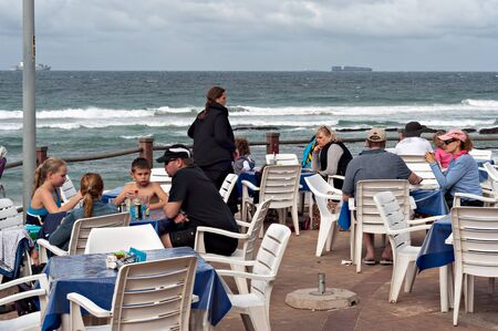 locals: DURBAN, SOUTH AFRICA - JULY 09, 2016: Locals and tourists at a restaurant on the promenade at the beach in Umhlanga Rocks beach