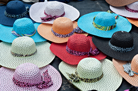 8d92f6c28 Brightly colored wide brimmed ladies straw sun hats for sale at the  beachfront Stock Photo -