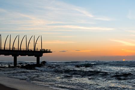 Mit Blick auf den Indischen Ozean durch die Millennium Pier in Umhlanga Rocks bei Sonnenaufgang