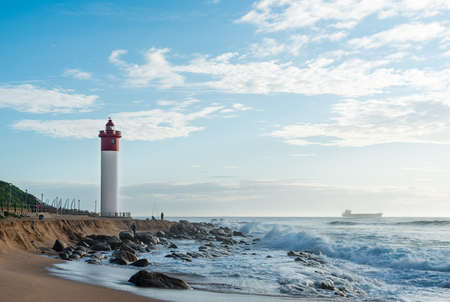 DURBAN, SOUTH AFRICA - MARCH 12, 2016: Umhlanga Rocks Lighthouse with fishermen and people walking on the promenade. Ship on the Indian Ocean in the background Banco de Imagens - 59472088