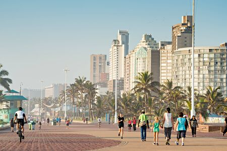 DURBAN, SOUTH AFRICA - APRIL 16, 2016: Locals and Tourists enjoying the Golden Mile Promenade just after sunrise.