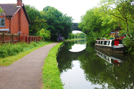 Birmingham canal boat with over arching bridge Stock Photo