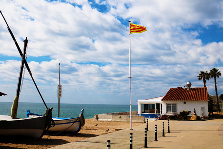 Spain beach front with boats, flag and summer house Stock Photo - 99599473
