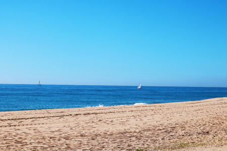 Spanish beach with small boat in the distance Stock Photo