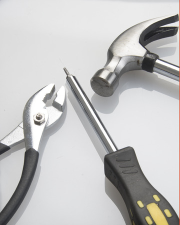 Product photograph of a pair of pliers,phillips screwdriver and hammer