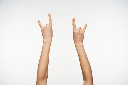 Indoor shot of attractive females's hands raised against white background, forming with fingers love sign. Women showing hand with sign language