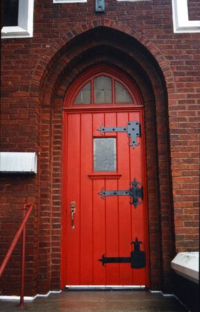 door knob: Red arched door on brick church Stock Photo