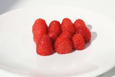 grouping: Grouping of raspberries on white plate Stock Photo