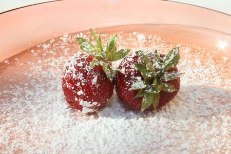 Two strawberries with powdered sugar on pink plate against a white background