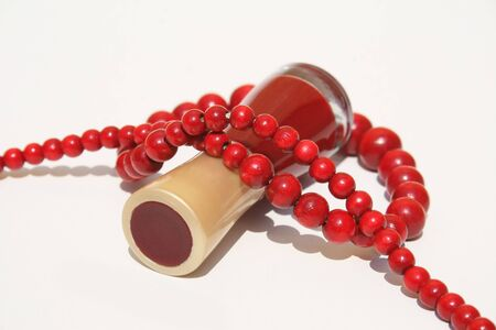 A bottle of red fingernail polish on side with strand of red wooden beaded necklace wrapped around