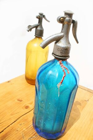 seltzer: Two antique seltzer bottles on weathered wooden table and white background