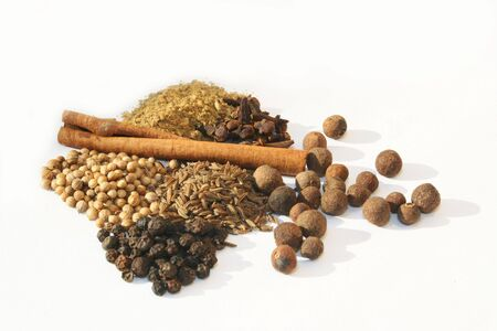 Various spices in piles against white background Stock Photo
