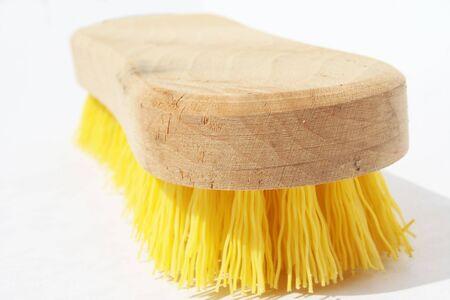 Scrub borstel met polyester gele haren en hout handvat tegen witte achtergrond