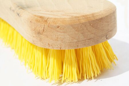 Scrub brush with polyester yellow bristles and wood handle against white background Stock Photo
