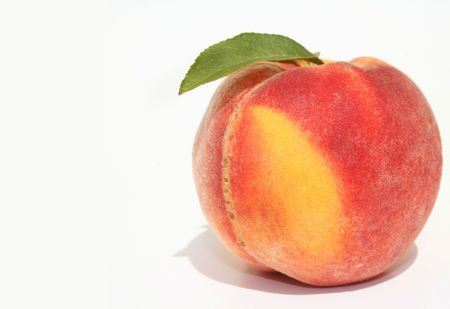 Single ripe peach with green leaves on white background