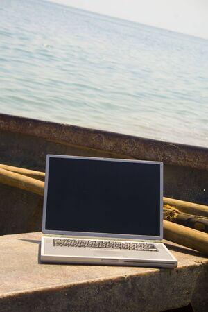 Close-up of laptop on bench of small fishing vessel