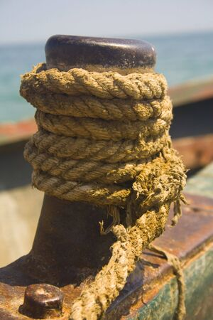 Close-up of rope wrapped around rusty fishing boat cleat