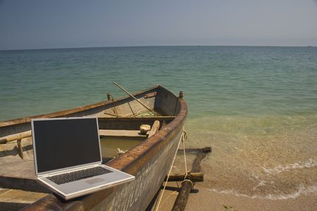 Laptop sitting on side of small fishing boat that is docked on beach