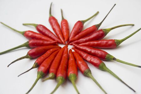 A pile of small red chili peppers arranged and isolated against a white background