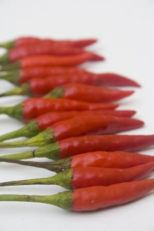 An arrangement of small red chili peppers isolated against a white background Stock Photo