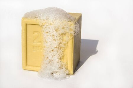 Square block of natural soap isolated against white background