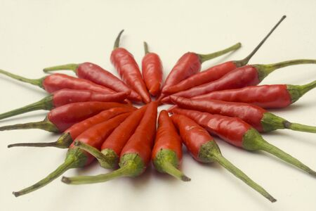 A pile of small red chili peppers arranged and isolated against a white background Stock Photo - 3495438