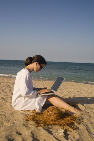 Woman sitting on beach in white dress working on laptop