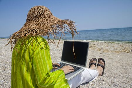 Woman sitting on beach in green top working on laptop Stock Photo - 3525278