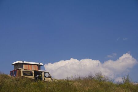 Van on cliff overlooking at beach with beautiful cloudscape Stock Photo