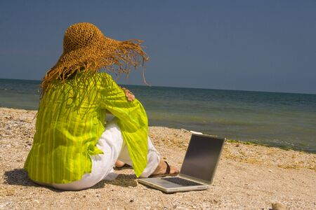 Woman in hat sitting on beach working on laptop Stock Photo
