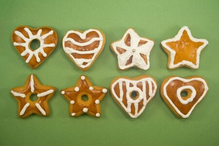 Two lines of star and heart shaped gingerbread cookies against green background