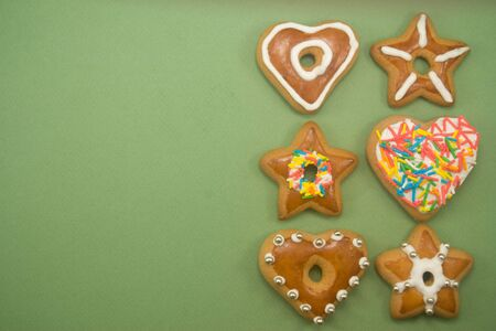 Six decorated gingerbread cookies on green with ad space on left Stock Photo