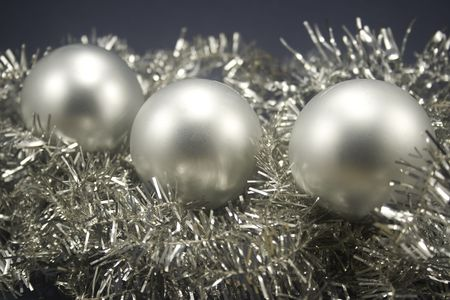 Three Christmas globes laying on tinsel Stock Photo