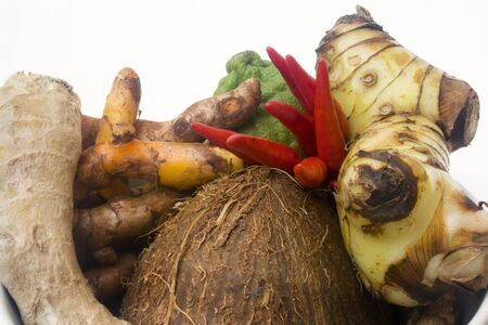 Coconut, small red chili pepperes, galangal root, kaffir lime, and tumeric in arrangement isolated against white