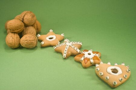 Christmas cookies and a pile of walnuts isolated on green paper Stock Photo
