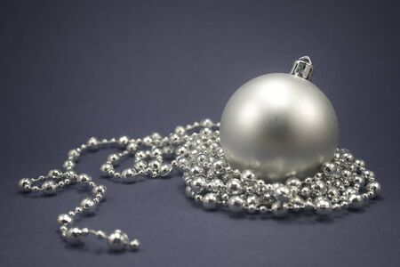 Single ornament with silver beaded string isolated on blue paper Stock Photo - 3847067