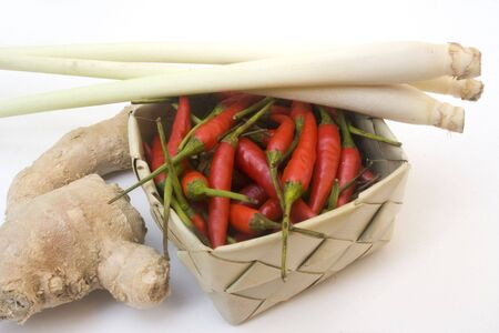 Basket of small chili peppers, ginger root, and lemon grass isolated on white Stock Photo