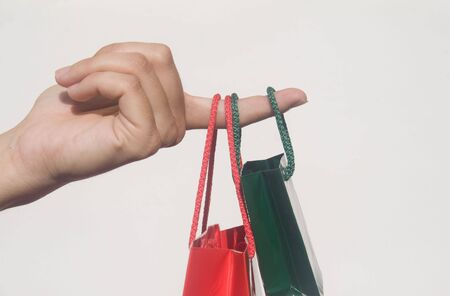 Finger holding two small shopping bags against white background Stock Photo - 3921170