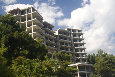 property development: Multilevel new cement building on hill in process of construction Stock Photo