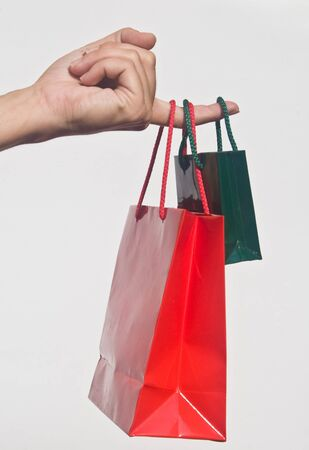Detail of hand holding two Christmas shopping bags against white background Stock Photo - 4007091