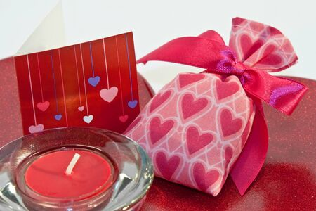 red metallic heart dish with heart sachet with card and candle Stock fotó