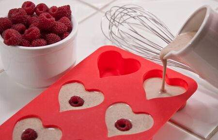 Whisk, bowl of raspberries and heart shaped muffin pan with pouring batter pitcher Stock Photo