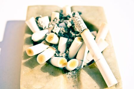 Close-up of a white stone square ashtray full of burnt cigarette butts