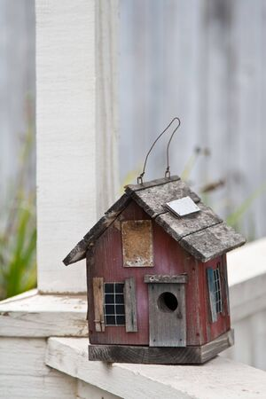 Country folk style bird house on front porch railing