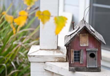 maison oiseau: Country style folk oiseau maison sur rambarde porche Banque d'images