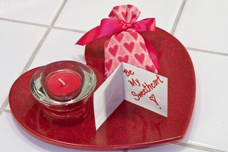 Red metallic heart dish with red candle in holder and valentine sachet with card photo