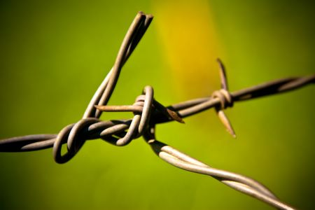 fencing wire: Macro of fencing wire against deeply out of focus green grass, focus on left of wire knot Stock Photo