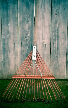 Used old flexible fork rake propped against a weathered gray wooden fence