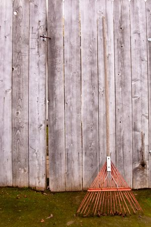 Used old flexible fork rake propped against a weathered gray wooden fence photo