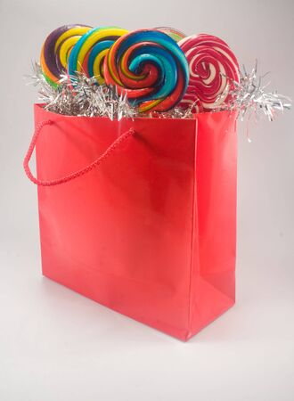 Shiny red gift bag filled with candy against plain background